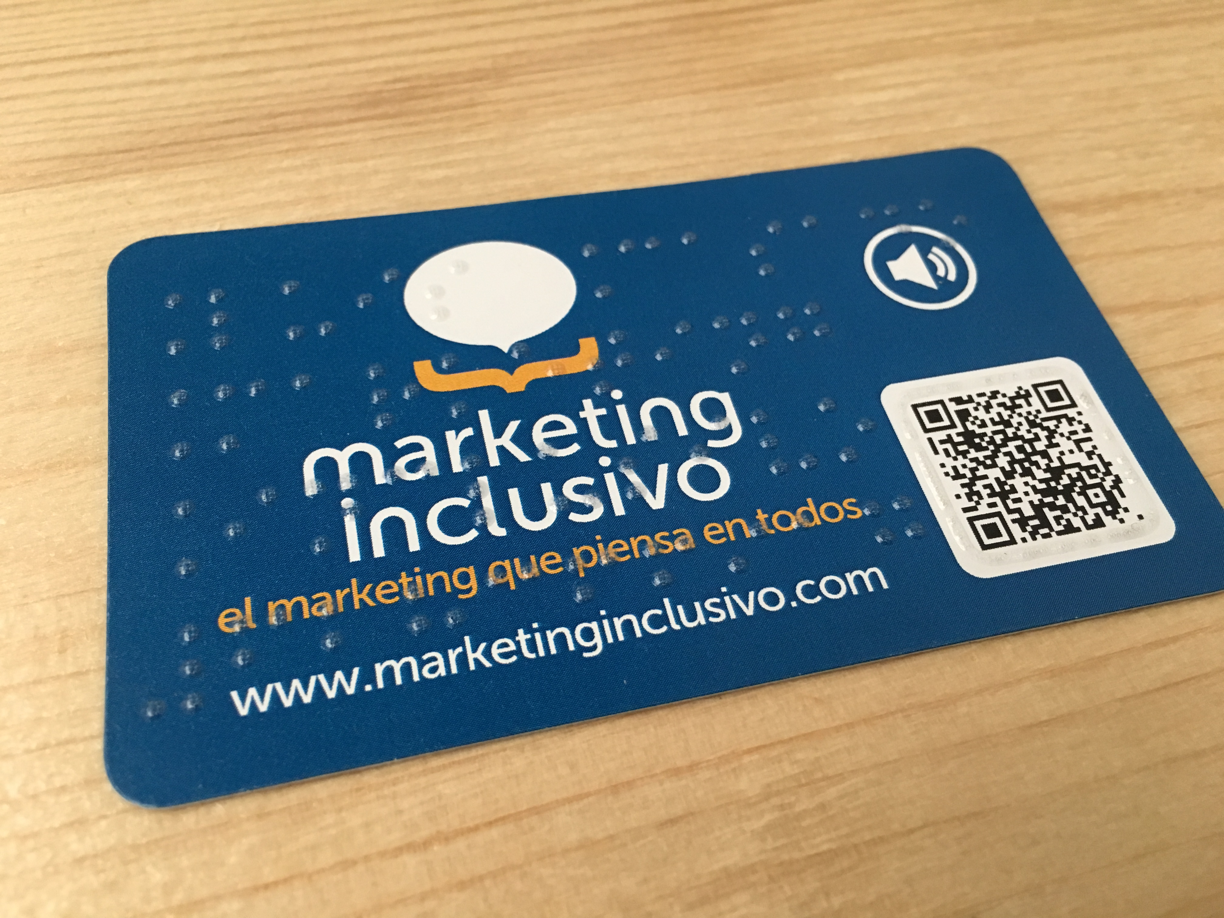 Tarjeta de visita azul de Marketing Inclusivo se aprecian unas letras en braille en toda su superficie y un código QR enmarcado con relieve braille.